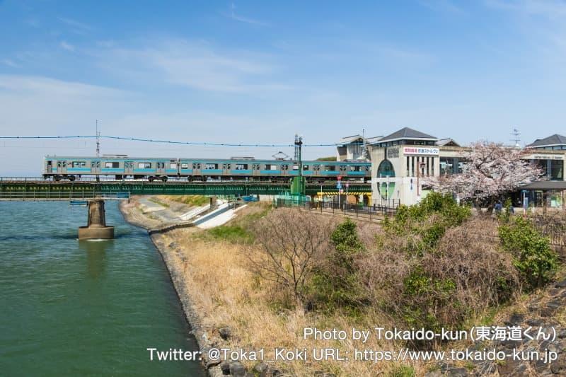 桜咲く宇治川を通過する205系