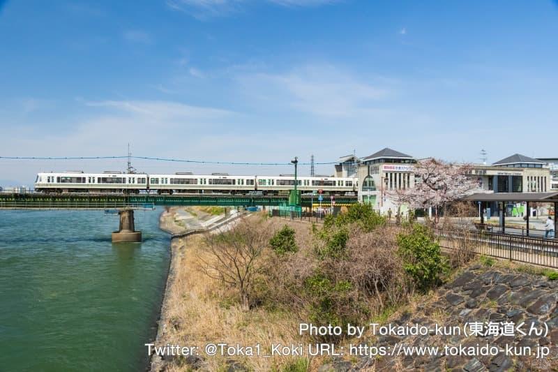 桜咲く宇治川を通過する221系